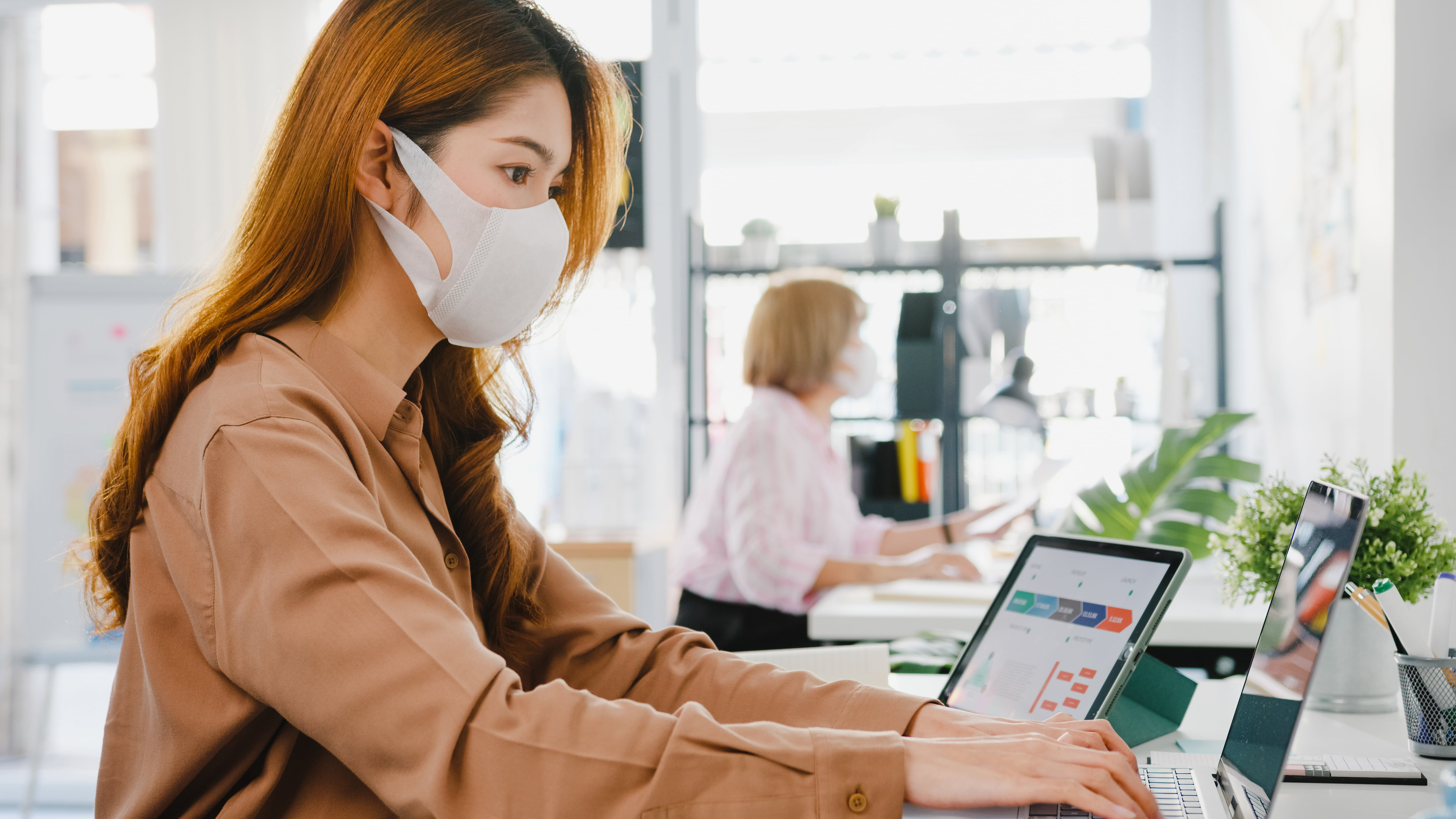 asia-businesswoman-entrepreneur-wearing-medical-face-mask-social-distancing-new-normal-situation-virus-prevention-while-using-laptop-back-work-office-min