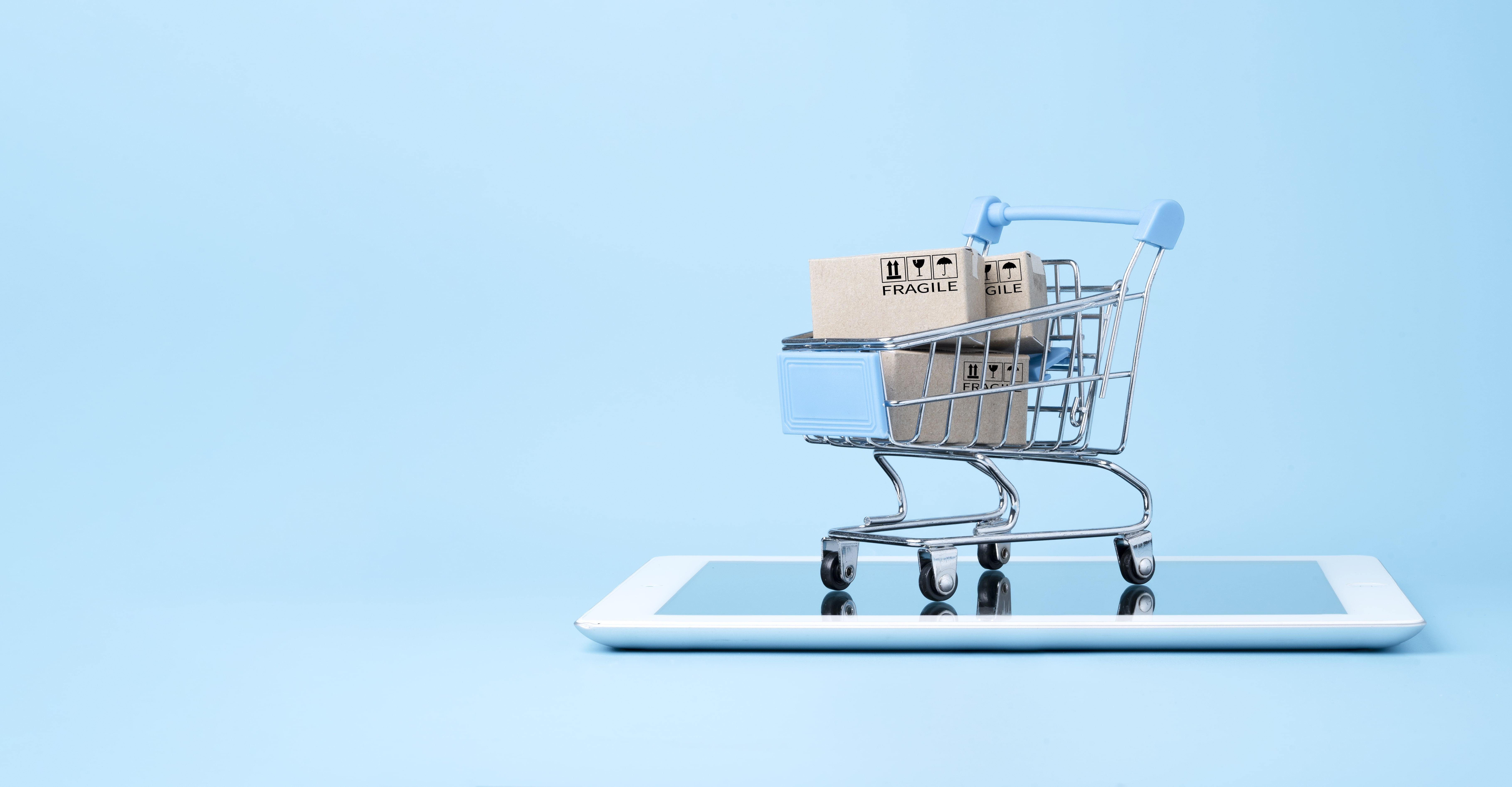 isolated-shipping-paper-boxes-inside-blue-shopping-cart-trolley-tablet-isolated-blue-min