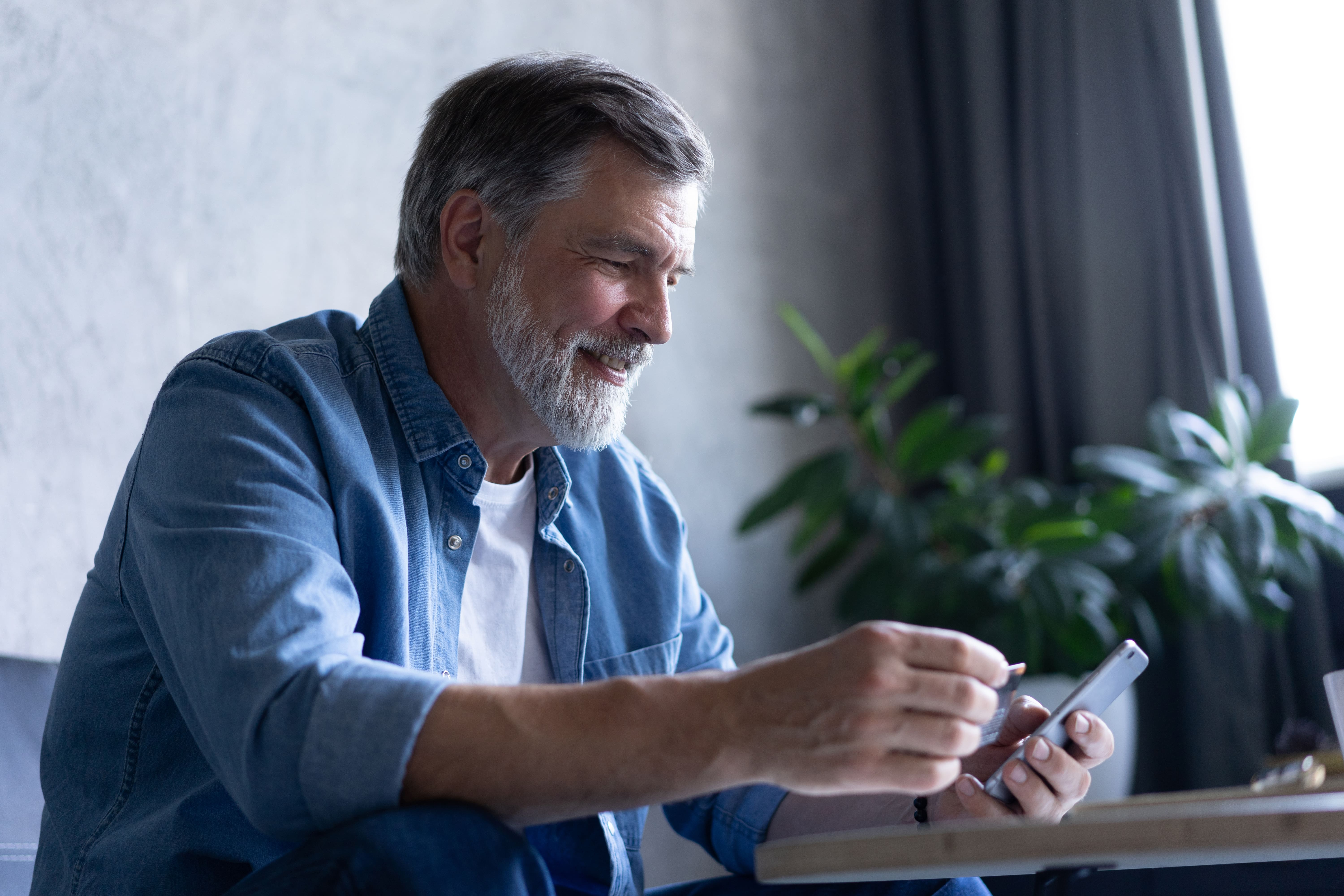 smiling-gray-haired-50s-man-pay-bills-online-using-modern-smartphone-gadget-credit-card-happy-mature-bank-client-make-internet-payment-purchase-cellphone-from-home-technology-concept-min